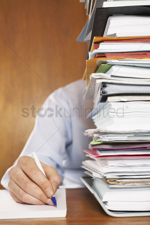 Retro : Man writing close-up of arm and hand sitting behind stack of paperwork at desk