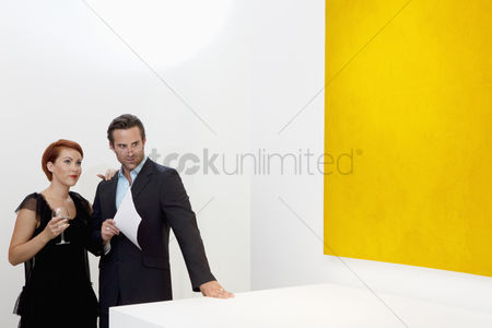 Interior background : Married young couple standing in art art gallery