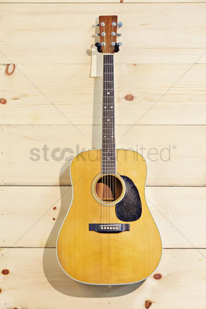 Arts : Martin guitar hanged against wood grain wall
