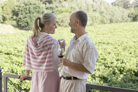 Toasting : Mature couple on terrace holding wine glasses
