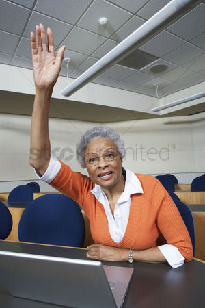 Arm raised : Mature female student raising hand in lecture theatre