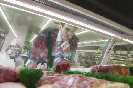 Supermarket : Mature man looks through glass of meat counter in supermarket