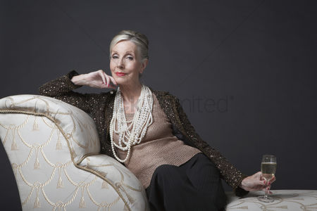 Posed : Mature woman having glass of champagne