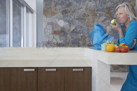 Grapes : Mature woman leaning on countertop eating apple side view
