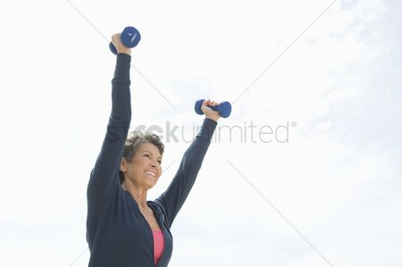 Dumbbell : Mature woman lifts dumbbells