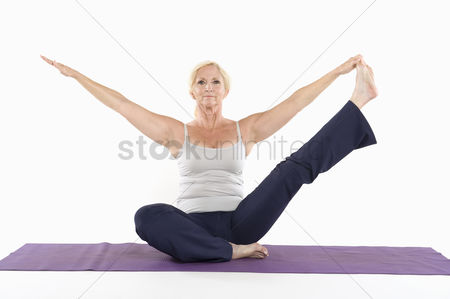 Fitness : Mature woman sitting on mat and doing yoga with arms outstretched