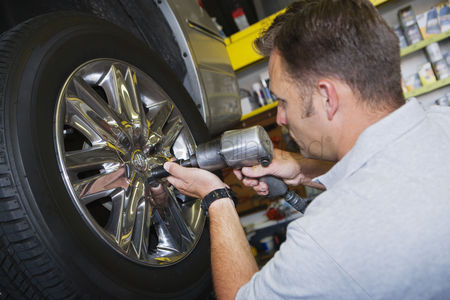 Transportation : Mechanic putting tire on a car