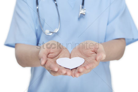 Medical personnel : Medical personnel showing a paper heart