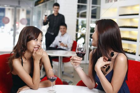 Toasting : Men flirting with women sitting at another table