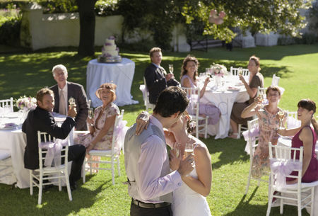 Dance : Mid adult bride and groom in garden among wedding guests holding wineglasses kissing