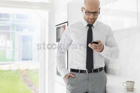Bald : Mid adult businessman text messaging through smart phone at home
