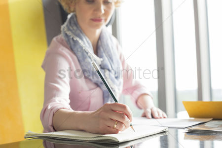 Notepad : Mid adult businesswoman writing on notepad at desk in office