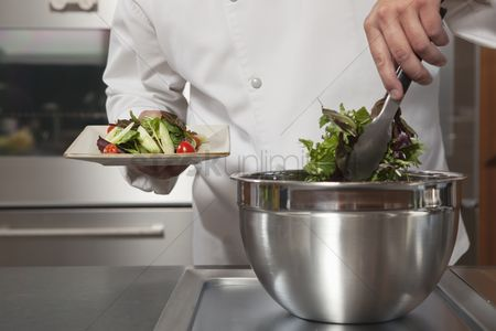 Bowl : Mid- adult chef lifts leaf vegetables onto side plate