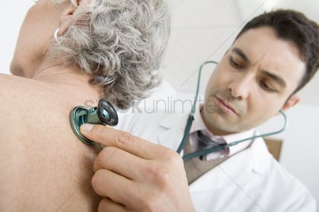 Examination : Mid adult doctor checks breathing of senior patient