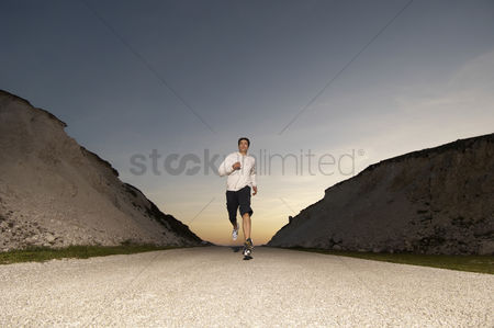 Remote : Mid adult man jogging in evening