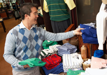 Shopping background : Mid-adult man looking at merchandise shopping in golf shop