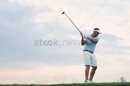 Sports : Mid-adult man playing golf against sky