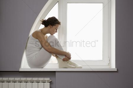 Interior : Mid adult woman sits on windowsill with ankles crossed