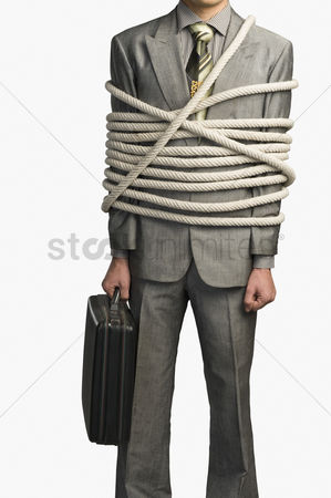 Forbidden : Mid section view of a businessman tied up with ropes