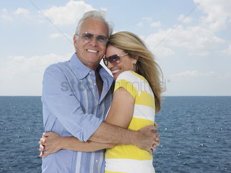 Relationships : Middle-aged couple embracing against sea portrait