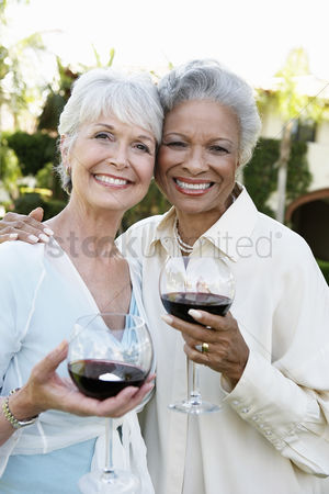 Friend : Middle-aged friends standing outside drinking wine from wineglasses