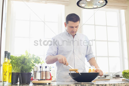 Houseplant : Middle-aged man preparing food in kitchen