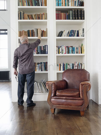 Choosing : Middle-aged man taking book from shelf back view