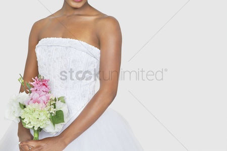 Flower : Midsection of bride holding bouquet over gray background
