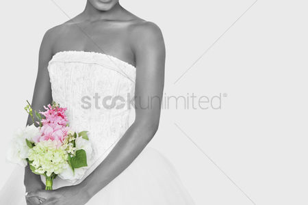 Day off : Midsection of bride holding bouquet over gray background