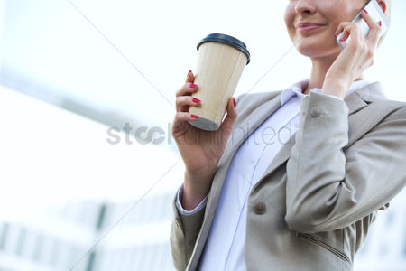 Cell phone : Midsection of businesswoman using cell phone while holding disposable cup outdoors