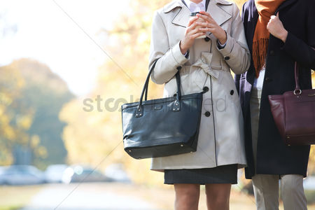 Jacket : Midsection of businesswomen carrying purses at park
