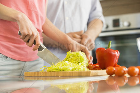 Couples : Midsection of woman chopping vegetables in kitchen with man standing in background
