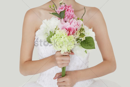Fashion : Midsection of young bride holding fresh bouquet