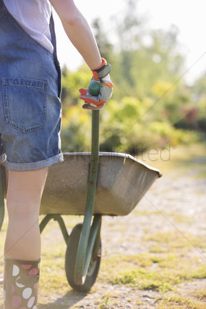 Pushing : Midsection rear view of female gardener pushing wheelbarrow at plant nursery