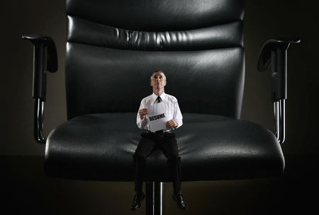Black background : Mini sized businessman sitting on a giant chair holding resume