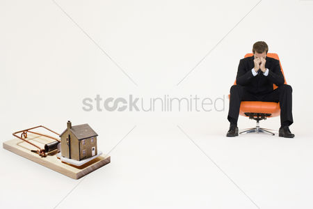 40 44 years : Model home on mouse trap with worried businessman sitting on chair representing increasing real estate rates