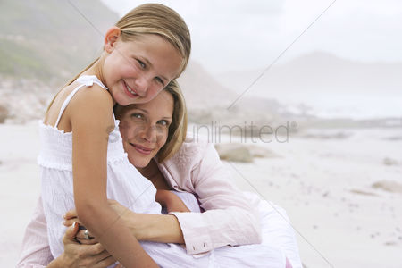 Closeness : Mother and daughter  7-9  hugging on beach portrait