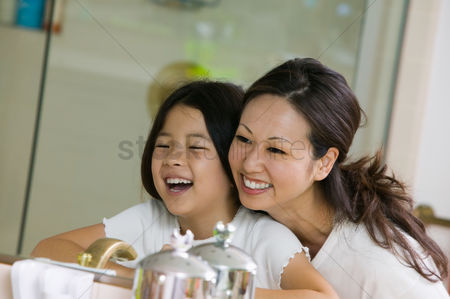 Interior : Mother and daughter looking at reflection in bathroom mirror focus on mirror