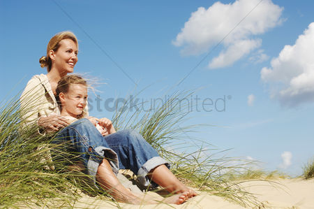 Daughter : Mother and daughter sitting on sand dune at beach