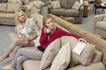 Furniture : Mother and daughter sitting on sofa while looking at price tag in furniture store