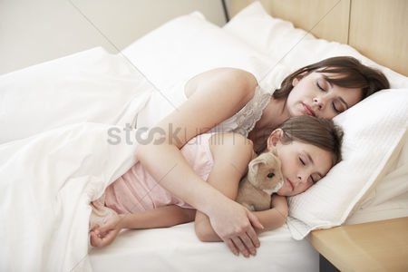 Toy : Mother and daughter sleeping in bed portrait