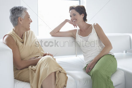 Daughter : Mother and daughter talking on sofa in living room