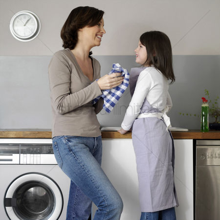 Denim : Mother and daughter washing the dishes together