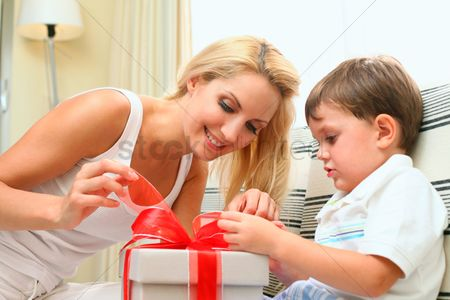 Birthday present : Mother and son opening a gift box together