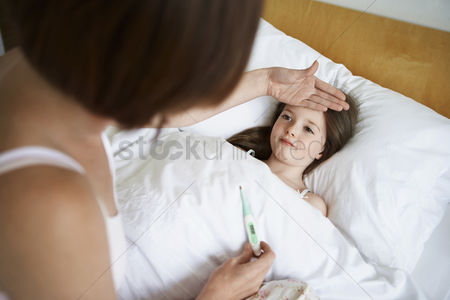Thermometer : Mother checking temperature of daughter in bed