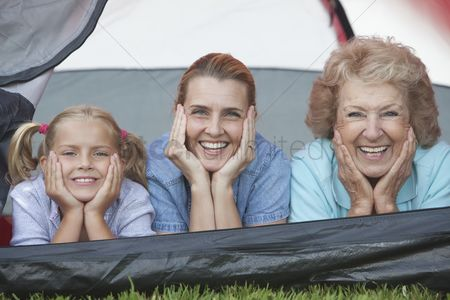 Pitch : Mother daughter and grand-daughter lean on elbows smiling from tent