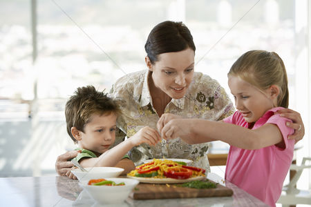 Ponytail : Mother helping children prepare a meal in kitchen
