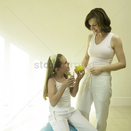 Appetite : Mother holding a green apple while daughter holding a glass of water