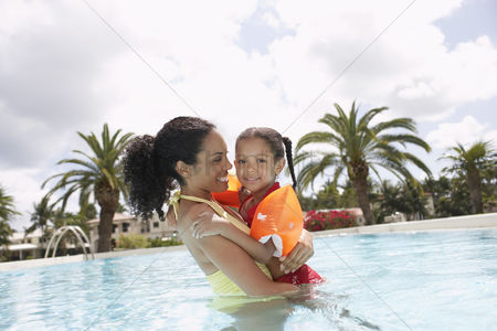 Ponytail : Mother holding daughter  5-6 years  in swimming pool portrait