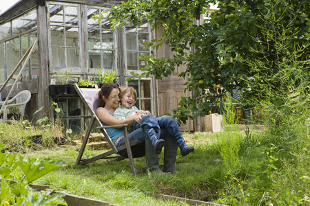 Greenhouse : Mother sitting with son in garden